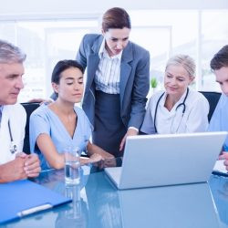A health care administrator meets with medical staff.