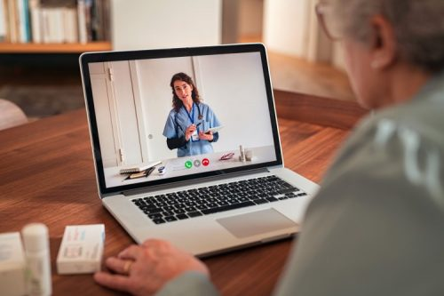 A patient communicates with a health care worker virtually on a laptop.