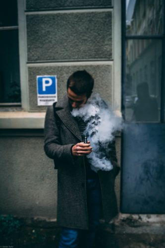 A young man uses his vape.