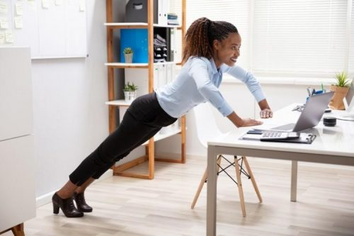 A businessperson doing some exercises at a workstation.