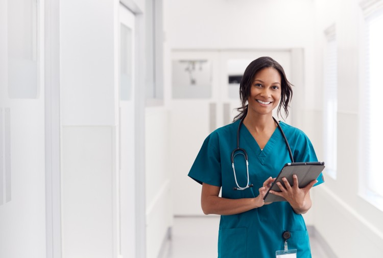 A smiling clinical research nurse holding a tablet.
