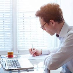 Man applying for jobs on laptop after MBA
