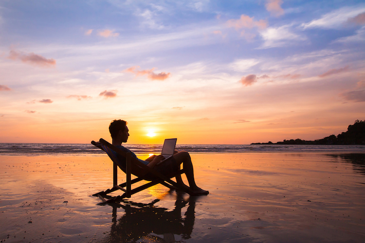 Freelancer working at the beach at sunset