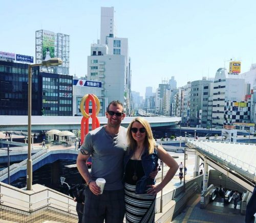 Heather and her husband pose for a picture in a busy downtown area of Japan.
