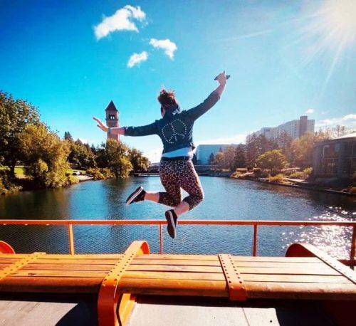WSU Online MBA student jumping on bridge near river