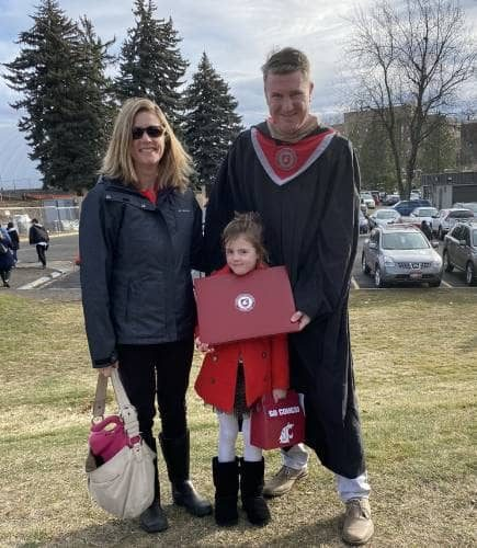 WSU Online EMBA student smiles with family at graduation