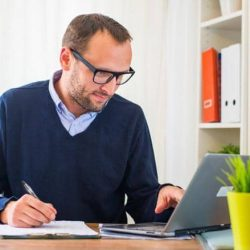 Man with glasses working from home