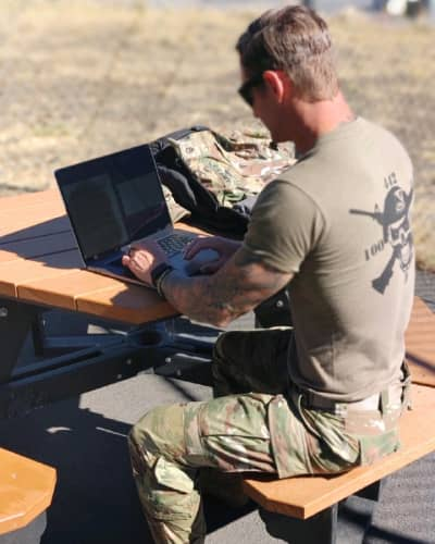 Man in military uniform works on MBA coursework on a laptop out in the field