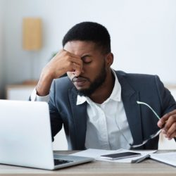 A tired professional sits at a computer.