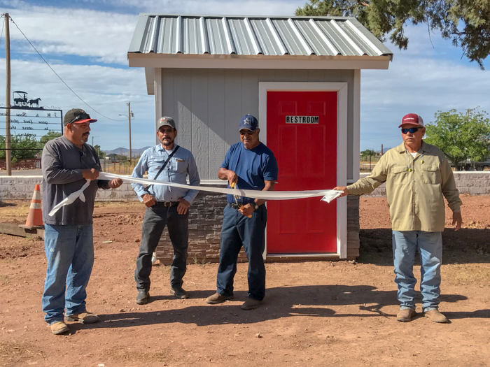 "County cemetery workers Joe Louis Sanchez, Manny Garcia, and Fernie Calderon help Mingo Corralez cut the ""ribbon"" officially opening of the new bathroom at the cemetery. County staff is already planning to add handicap access to the much-needed addition. -Photo by Gilda Morales"