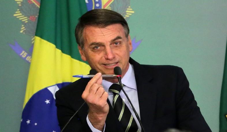 air Bolsonaro mostra caneta utilizada para assinar decreto que flexibilizou posse de armas; ato foi revogado posteriormente, mas o presidente voltou a assinar novos decretos sobre o tema, que é uma promessa de campanha