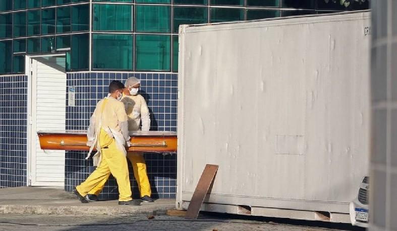 Agentes funerários levam caixão para retirar corpo em contêiner frigorífico, no Rio de Janeiro