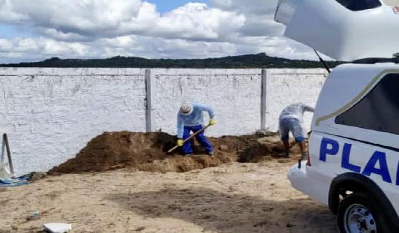 Funcionários da prefeitura fazendo a cova no cemitério da cidade