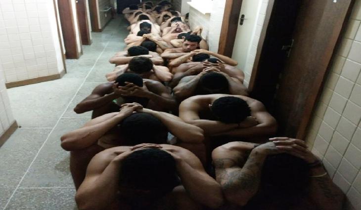 Presos reunidos em corredor, após fuga frustrada; ao lado, buraco que serviria para escapar