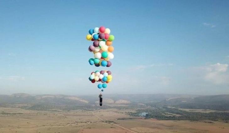nglês atravessou 25 quilômetros suspenso por 100 balões de gás hélio