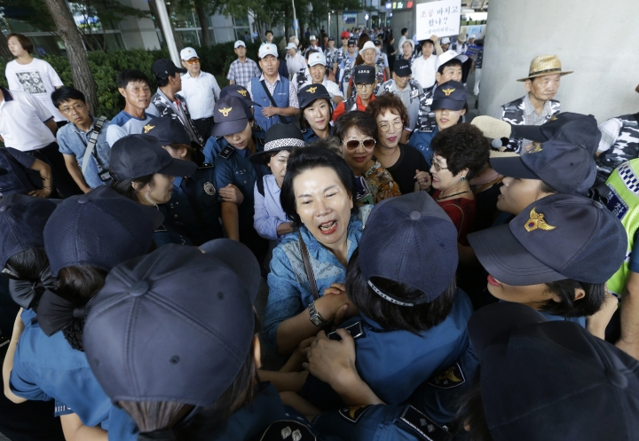 South Korean protesters are surrounded by police officers as they oppose South Korean lawmakers returning from their visit to China at Incheon International Airport in Incheon, South Korea, Wednesday, Aug. 10, 2016. A group of lawmakers from the main opposition Minjoo Party of Korea visited China on Monday, Aug. 8, for talks with Chinese officials and scholars over the planned deployment of an advanced U.S. anti-missile system to South Korea, a major thorn in relations between South Korea and China. (AP Photo/Ahn Young-joon)