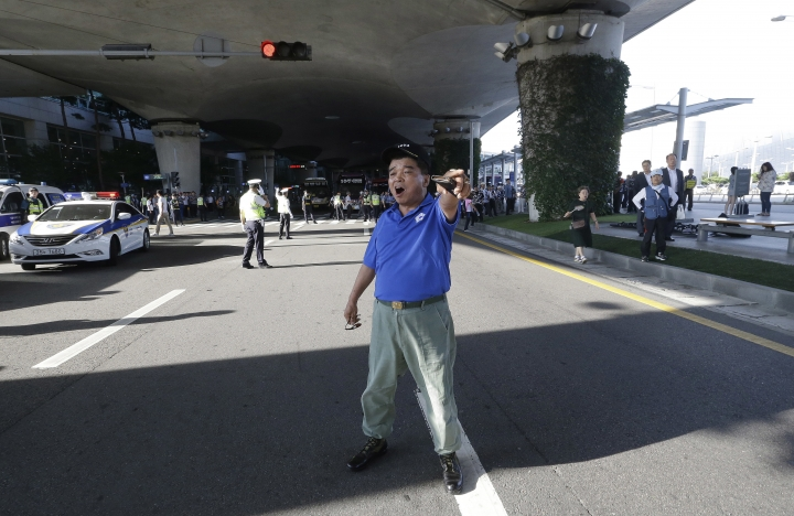 A South Korean war veteran shouts to oppose South Korean lawmakers's return from their visit to China at Incheon International Airport in Incheon, South Korea, Wednesday, Aug. 10, 2016. A group of lawmakers from the main opposition Minjoo Party of Korea visited China on Monday, Aug. 8, for talks with Chinese officials and scholars over the planned deployment of an advanced U.S. anti-missile system to South Korea, a major thorn in relations between South Korea and China. (AP Photo/Ahn Young-joon)