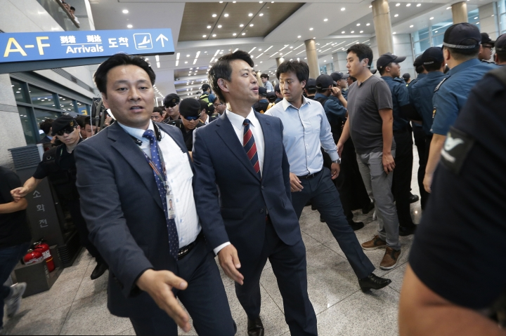 Rep. Kim Young-ho, center, of South Korean main opposition Minjoo Party is escorted by plain clothed police officers after returning from China at the Incheon International Airport in Incheon, South Korea, Wednesday, Aug. 10, 2016. A group of lawmakers from the main opposition Minjoo Party of Korea visited China on Monday, Aug. 8, for talks with Chinese officials and scholars over the planned deployment of an advanced U.S. anti-missile system to South Korea, a major thorn in relations between South Korea and China. (AP Photo/Ahn Young-joon)