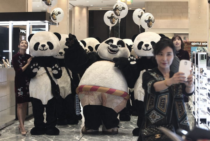 FILE - In this Thursday, April 28, 2016 file photo, a woman takes a selfie with workers wearing panda costumes during a promotion event for Chinese tourists at a department store in Seoul, South Korea. Chinese anger at South Korea over its decision to deploy an U.S. anti-missile defense system appears to be threatening everything from appearances by the stars of K-Pop to future cooperation on North Korea at the United Nations. (AP Photo/Ahn Young-joon, File)
