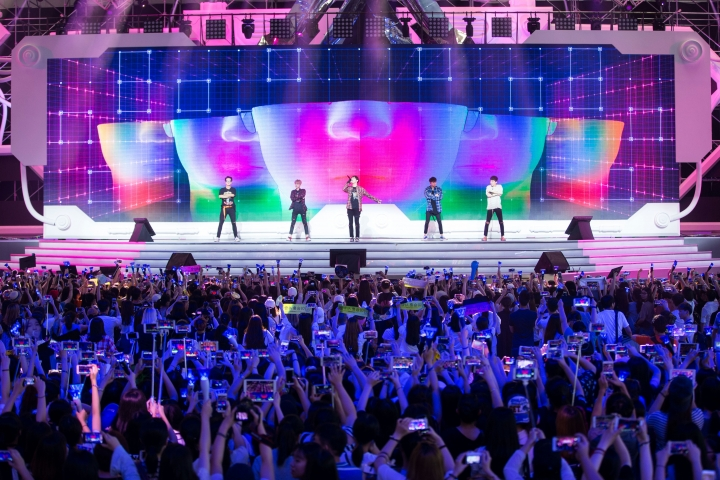 In this Friday, July 22, 2016 photo, Chinese fans take photos of the South Korean K-Pop group Winner during a concert in Shanghai. Chinese anger at South Korea over its decision to deploy an U.S. anti-missile defense system appears to be threatening everything from appearances by the stars of K-Pop to future cooperation on North Korea at the United Nations. (Chinatopix via AP)