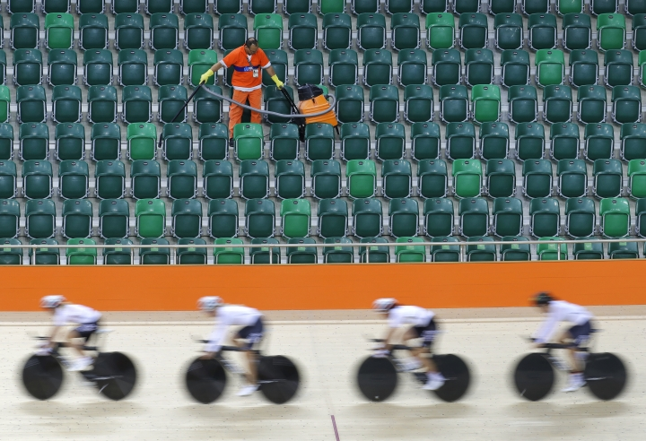 A worker vacuums spectator seating as members of the German women's track cycling team round the track during a training session inside the Rio Olympic Velodrome in advance of the 2016 Olympic Games in Rio de Janeiro, Brazil, Thursday, Aug. 4, 2016. (AP Photo/Patrick Semansky)