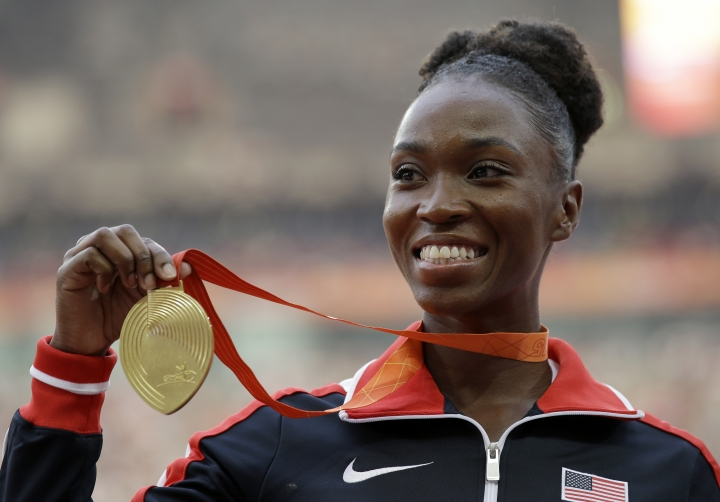 FILE - In this Aug. 29, 2015, women's long jump gold medalist United States' Tianna Bartoletta celebrates on the podium at the World Athletics Championships at the Bird's Nest stadium in Beijing. Bartoletta is going for gold at the 2016 Summer Olympics in both the 100 meters and the long jump. She's got her daily plans written on laminated cards that she brings with her to the track. (AP Photo/Kin Cheung, File)