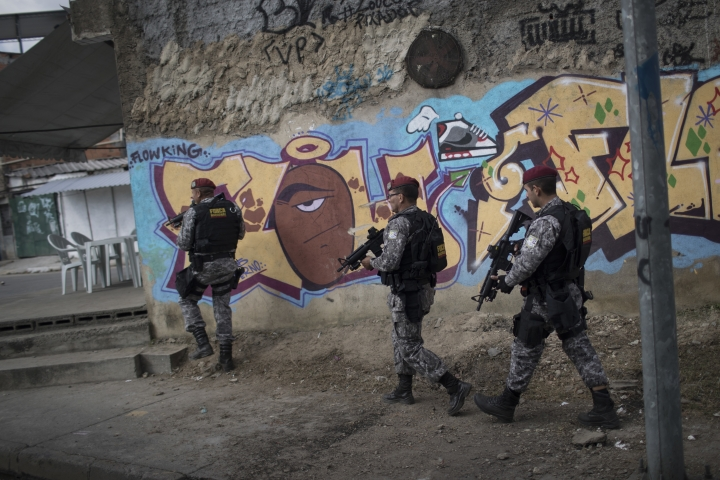 Brazil's national security force officers move inside the Vila do Joao, part of the Mare complex of slums during a police operation in search for criminals during the 2016 Summer Olympics in Rio de Janeiro, Brazil, Thursday, Aug. 11, 2016. A police officer is recovering from a life-saving surgery after he and two others sent to Rio de Janeiro for the Olympics were shot at after getting lost near a slum. (AP Photo/Felipe Dana)