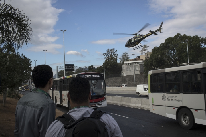 A Brazil's national security force helicopter flies over Avenida Brasil during a police operation in search for criminals at the Mare complex of slums during the 2016 Summer Olympics in Rio de Janeiro, Brazil, Thursday, Aug. 11, 2016. A police officer is recovering from a life-saving surgery after he and two others sent to Rio de Janeiro for the Olympics were shot at after getting lost near a slum. (AP Photo/Felipe Dana)