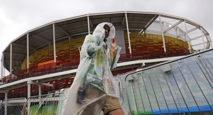 A volunteer covers up under a poncho during a shower outside the Olympic Tennis Center at the 2016 Summer Olympics in Rio de Janeiro, Brazil, Wednesday, Aug. 10, 2016. Rain delayed the start of play. (AP Photo/Charles Krupa)