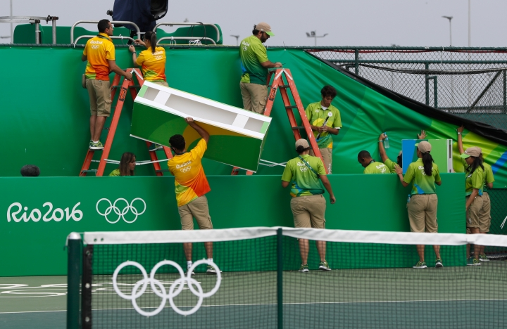 Volunteers work to repair wind damage on a court during the tennis competition at the 2016 Summer Olympics in Rio de Janeiro, Brazil, Sunday, Aug. 7, 2016. Because of wind that reached 25 mph (40 kph), the start of Sunday's play in the Rio de Janeiro Olympic tennis tournament was delayed on all courts except the main stadium, some matches started about 2 hours late.(AP Photo/Vadim Ghirda)