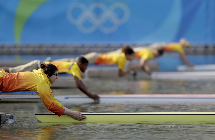 Volunteers hold the sculls as rowers wait for the start of the men's rowing single sculls quarterfinal heats during the 2016 Summer Olympics in Rio de Janeiro, Brazil, Tuesday, Aug. 9, 2016. (AP Photo/Luca Bruno)