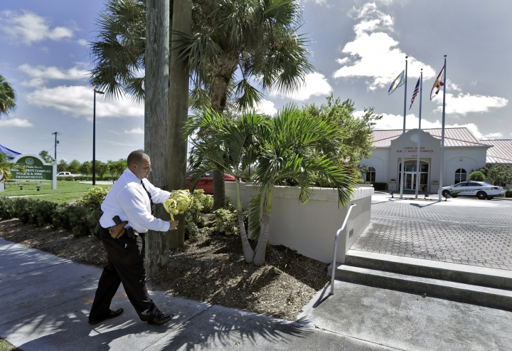 """Punta Gorda Police Dept. Det. J. Davoult takes down crime scene tape outside Public Safety Complex Wednesday, Aug. 10, 2016, in Punta Gorda, Fla. Police say an officer accidentally shot a woman to death during a citizen's academy """"shoot/don't shoot"""" exercise Tuesday evening. (AP Photo/Chris O'Meara)"""