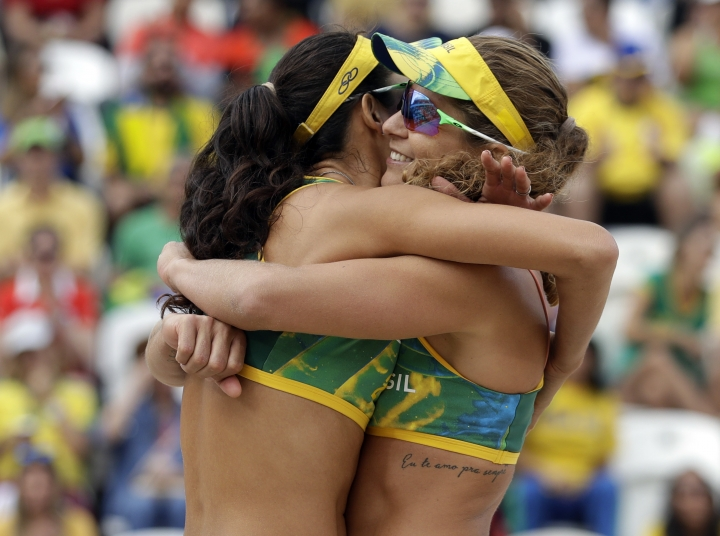 Brazil's Larissa Franca, right, and Talita Rocha celebrate a point over Poland during a women's beach volleyball match at the 2016 Summer Olympics in Rio de Janeiro, Brazil, Thursday, Aug. 11, 2016. (AP Photo/Marcio Jose Sanchez)