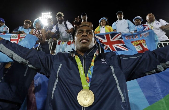 Viliame Mata, of Fiji, poses with fans after winning the gold medal match against Britain in the mens rugby sevens at the 2016 Summer Olympics in Rio de Janeiro, Brazil, Thursday, Aug. 11, 2016. (AP Photo/Robert F. Bukaty)