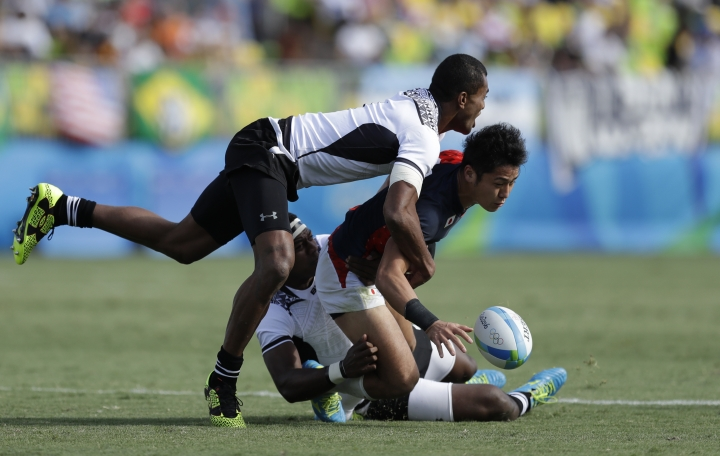 Japan's Teruya Goto, front, is tackled by Fiji's Apisai Domolailai, left, and teammate Ro Dakuwuqa, during the semi final of the men's rugby sevens match at the Summer Olympics in Rio de Janeiro, Brazil, Thursday, Aug. 11, 2016. (AP Photo/Themba Hadebe)