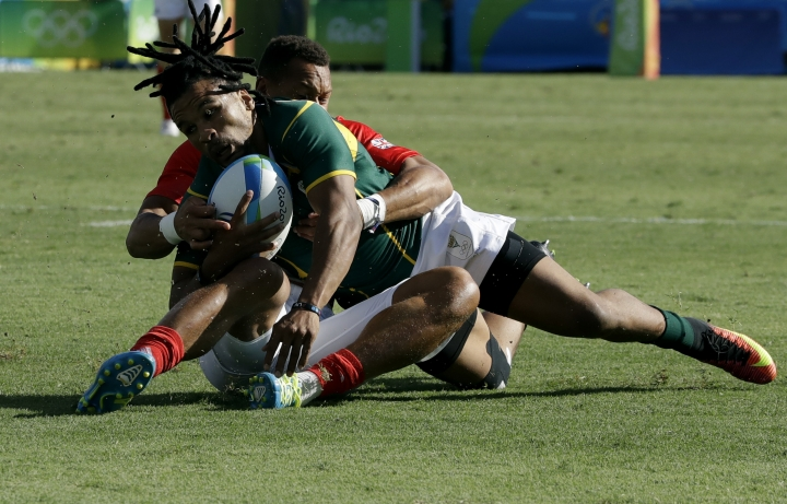 South Africa's Rosko Specman, front, is tackled by Britain's Daniel Bibby, during the semi final of the men's rugby sevens match at the Summer Olympics in Rio de Janeiro, Brazil, Thursday, Aug. 11, 2016. (AP Photo/Themba Hadebe)