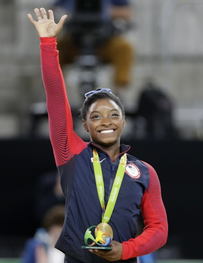United States' Simone Biles waves on the podium after receiving her gold medal in the artistic gymnastics women's individual all-around final at the 2016 Summer Olympics in Rio de Janeiro, Brazil, Thursday, Aug. 11, 2016. (AP Photo/David Goldman)