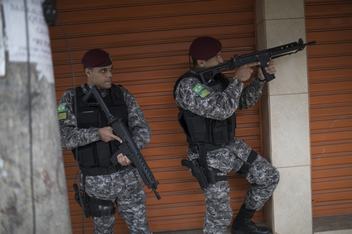 Brazil's national security force officers aim their weapons during a police operation in search for criminals in Vila do Joao, part of the Mare complex of slums during the 2016 Summer Olympics in Rio de Janeiro, Brazil, Thursday, Aug. 11, 2016. A police officer is recovering from a life-saving surgery after he and two others sent to Rio de Janeiro for the Olympics were shot at after getting lost near a slum. (AP Photo/Felipe Dana)