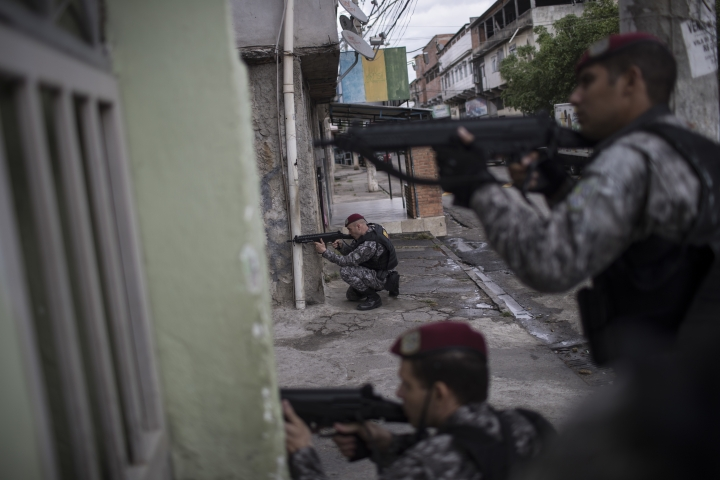Brazil's national security force officers aim their weapons during a police operation in search for criminals in Vila do Joao, part of the Mare complex of slums during the Summer Olympics in Rio de Janeiro, Brazil, Thursday, Aug. 11, 2016. A police officer is recovering from a life-saving surgery after he and two others sent to Rio de Janeiro for the Olympics were shot at after getting lost near a slum. (AP Photo/Felipe Dana)