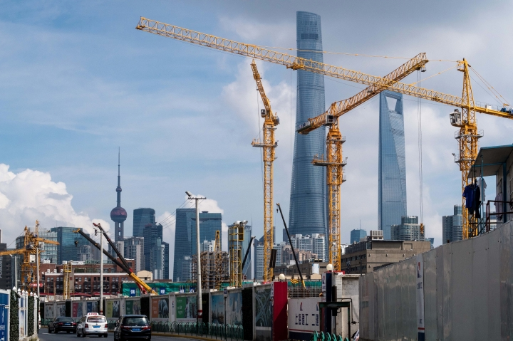 In this Friday, Aug. 5, 2016 photo, cranes work at a construction site near skyscrapers in the Lujiazui financial district of Shanghai. A Chinese official tried Friday, Aug. 12, to reassure companies and investors that China's economic growth is stable despite unexpectedly weak July activity but acknowledged it faces pressure from lackluster global demand. (Chinatopix via AP)