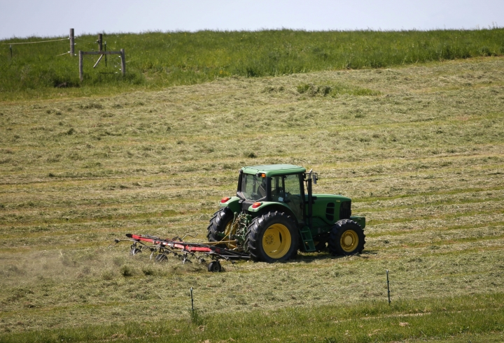 FILE - In this Friday, May 20, 2016, file photo, a worker rakes hay at a farm on a warm spring day in Kinderhook, N.Y. On Friday, Aug. 12, 2016, the Labor Department reports on producer prices during July. (AP Photo/Mike Groll, File)