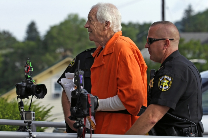 Former Penn State University assistant football coach Jerry Sandusky, center, arrives at the Centre County Courthouse for an appeals hearing about whether he was improperly convicted four years ago, in Bellefonte, Pa. Friday, Aug. 12, 2016. (AP Photo/Gene J. Puskar)