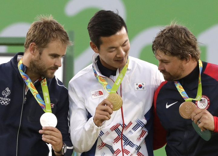 Gold medal winner Ku Bon-chan of South Korea, center, celebrates on the podium with silver medalist Jean Charles Valladont, left, and bronze medalist Brady Ellison of the United States at the awards ceremony of the men's individual archery competition at the Sambadrome venue during the Summer Olympics in Rio de Janeiro, Brazil, Friday, Aug. 12, 2016. (AP Photo/Alessandra Tarantino)