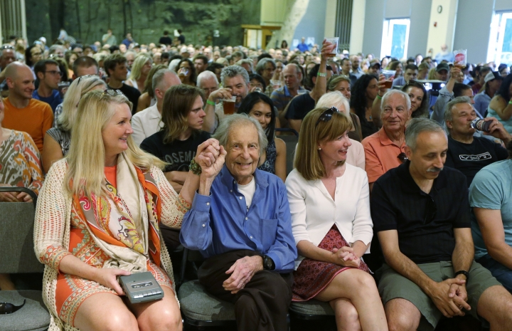 "In this photo taken July 26, 2016 in Seattle, legendary mountain climber Fred Beckey, second from lower left, sits next to Megan Bond, left, his friend and companion, as he is introduced at a sold-out promotional event for ""Dirtbag: The Legend of Fred Beckey,"" an upcoming documentary feature film about his life in Seattle. Beckey, 93, has bagged more first ascents than any other mountaineer and wrote the definitive guidebooks to a major North American mountain range. (AP Photo/Ted S. Warren)"