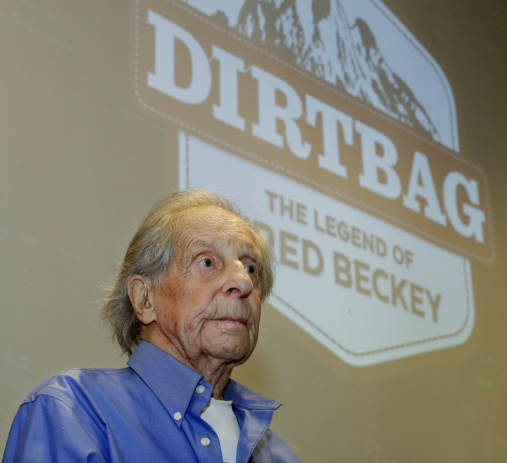 """In this photo taken July 26, 2016 in Seattle, Fred Beckey, the legendary mountain climber who has bagged more first ascents than any other mountaineer and wrote the definitive guidebooks to a major North American mountain range, sits in front of a screen bearing the logo for """"Dirtbag: The Legend of Fred Beckey,"""" an upcoming documentary feature film about his life. Beckey, 93, was waiting to begin narrating a personal slide show to a sold-out crowd at an event to kick-off a funding drive for the movie. (AP Photo/Ted S. Warren)"""