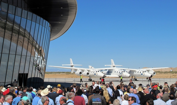 FILE - This Oct. 17, 2011, file photo shows a crowd gathered outside Spaceport America for a dedication ceremony as Virgin Galactic's mothership WhiteKnightTwo sits on the tarmac near Upham, N.M. New Mexico Spaceport Authority director Christine Anderson, who is resigning, said the spaceport is on the right track and she believes it will be a game changer for New Mexico. (AP Photo/Susan Montoya Bryan, File)