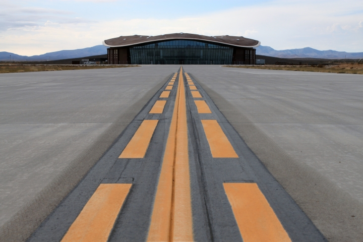 FILE - This Dec. 9, 2014, file photo shows the taxiway leading to the hangar at Spaceport America in Upham, N.M. New Mexico Spaceport Authority director Christine Anderson, who is resigning, said the spaceport is on the right track and she believes it will be a game changer for New Mexico. (AP Photo/Susan Montoya Bryan)