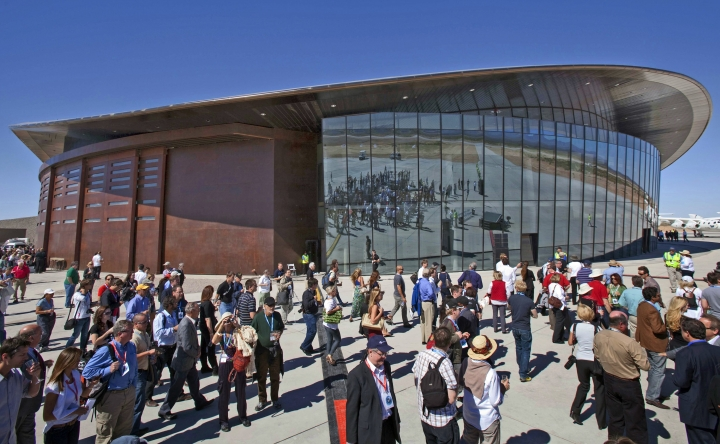 FILE - In this Oct. 17, 2011, file photo, guests stand outside the new Spaceport America hangar in Upham, N.M. New Mexico Spaceport Authority director Christine Anderson, who is resigning, said the spaceport is on the right track and she believes it will be a game changer for New Mexico, (AP Photo/Matt York, File)