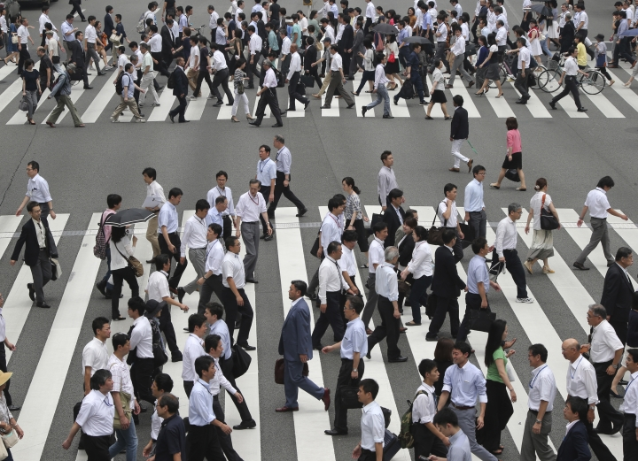 In this July 1, 2016 photo, people cross a street in Tokyo, Friday, July 1, 2016. Japan's economy grew at a slower than forecast 0.2 percent annual rate in the April-June quarter, as the recovery was sapped by weaker exports and business investment, the government said Monday, Aug. 15, 2016. (AP Photo/Koji Sasahara)