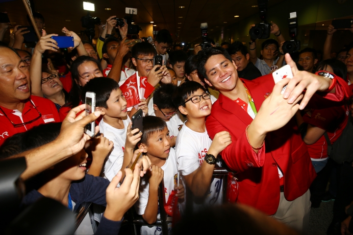 Singaporean swimmer Joseph Schooling, front right, poses for a photo with people at the Singapore Changi Airport in Singapore Monday, Aug. 15, 2016. Schooling won gold medal in the men's 100-meter butterfly and made history by winning the country's first gold medal at the 2016 Summer Olympics in Rio de Janeiro, Brazil. (AP Photo/Yong Teck Lim)